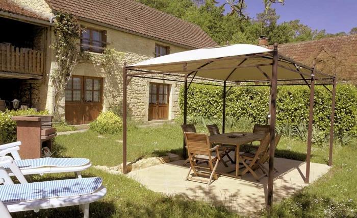 """l'entrée du gite """"Olivier"""" avec son terrain, la pergola, la table à manger, le barbecue et les fauteuils de jardin."""
