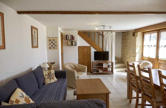 le salon avec son canapé et la porte fenêtre donnant sur le jardin