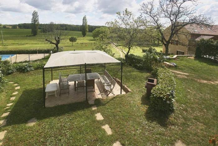 vue sur la terrasse, sa pergola et les champs autour.